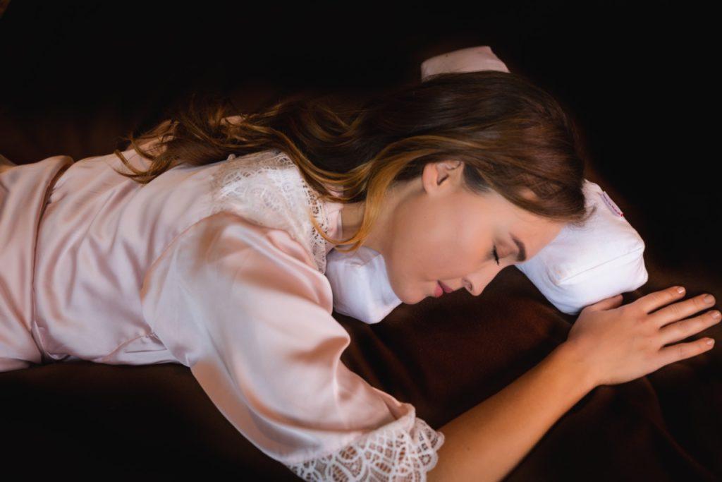 Viser kvinne som sover på magen med Face in Place puten